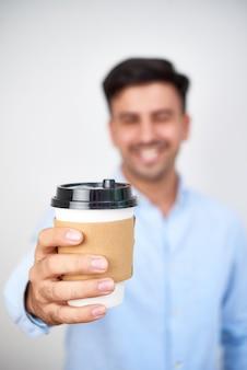 Мужчина держит бумажный стаканчик кофе