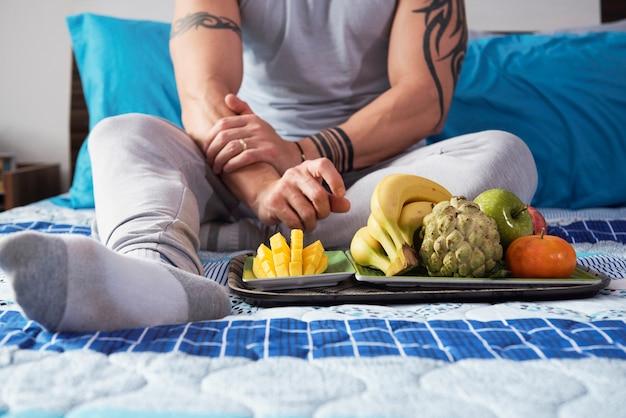 熟した果物を持つ男