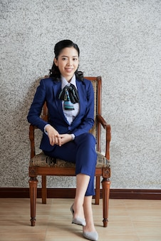 Элегантная деловая женщина сидит в кресле