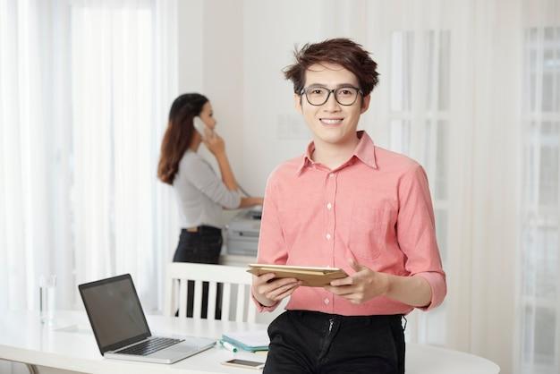 オフィスでタブレットと笑みを浮かべて男