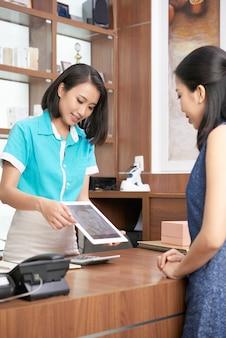 Женщина показывая таблетку к милому клиенту салона курорта