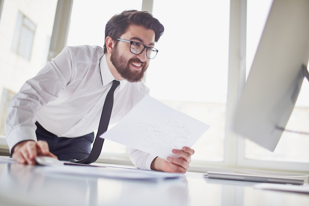 Исполнительный проведение бумаги и глядя на компьютере