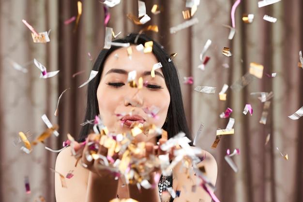 Женщина выдувает конфетти