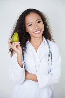 Доктор держит спелую грушу