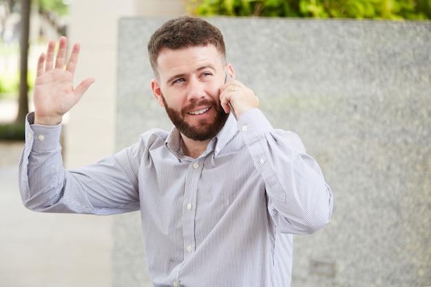 電話で話しているフレンドリーなビジネスマン