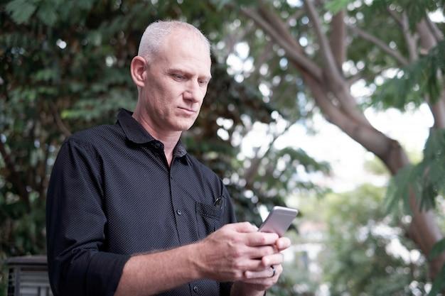 スマートフォンを使用して年配の男性