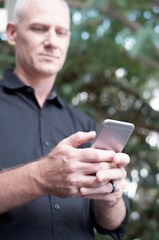 スマートフォンで男のテキストメッセージ