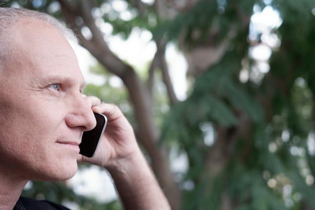スマートフォンで話している男性