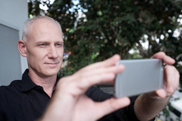 スマートフォンで写真を撮る男