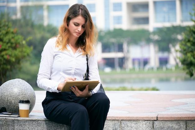 Бизнес леди, чтение документа на планшете