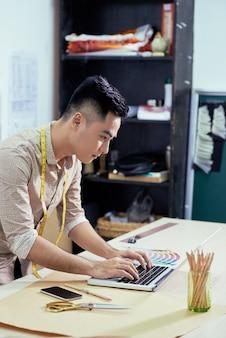 Дизайнер работает на ноутбуке в студии