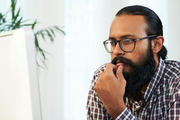 Бородатый программист смотрит на экран