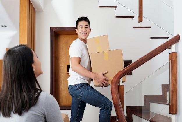 Молодая пара смешанной расы приносит картонные коробки в свою новую квартиру