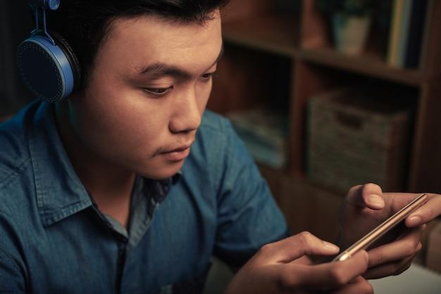 スマートフォンでゲームをプレイする男