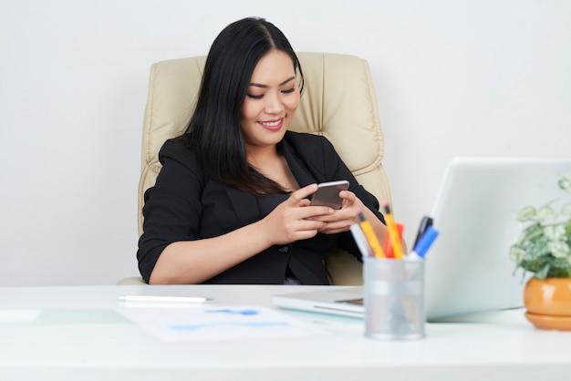美しいビジネス女性のテキストメッセージ