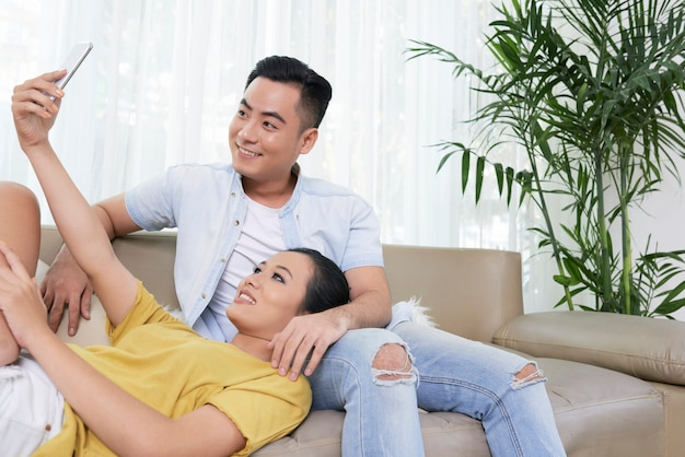 Современная пара, принимая селфи на диване у себя дома