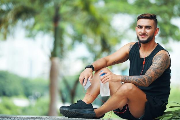 Уверенный спортсмен с телефоном, сидя на открытом воздухе