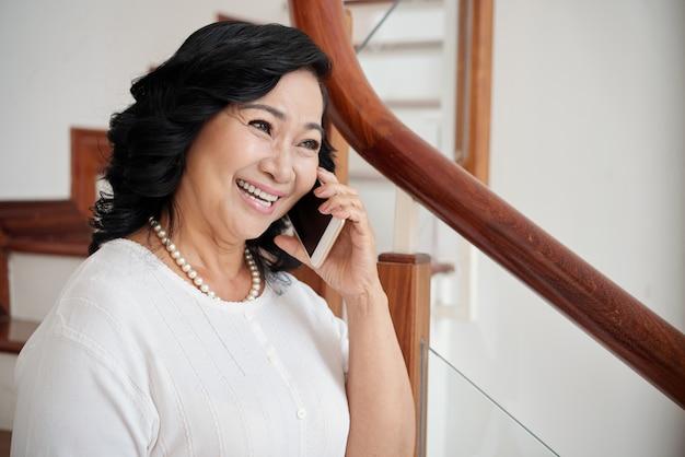 Веселая женщина разговаривает по телефону