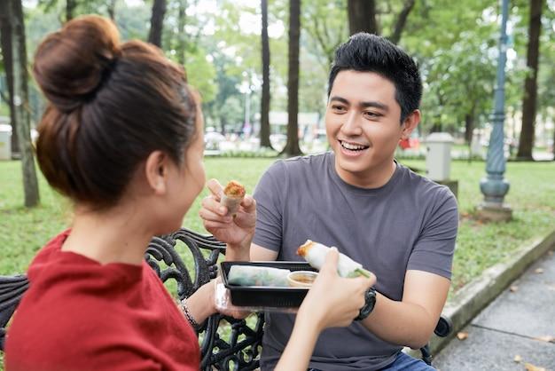Молодой человек кормит подругу