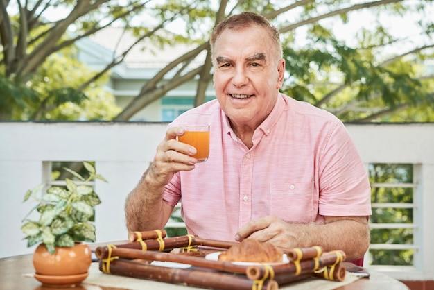 新鮮なジュースを楽しんでいる笑みを浮かべて男