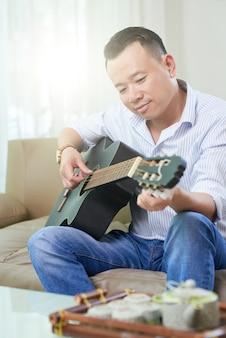 Человек учится играть на гитаре