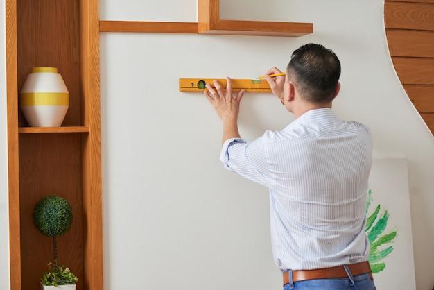 Мужчина украшает стену картиной