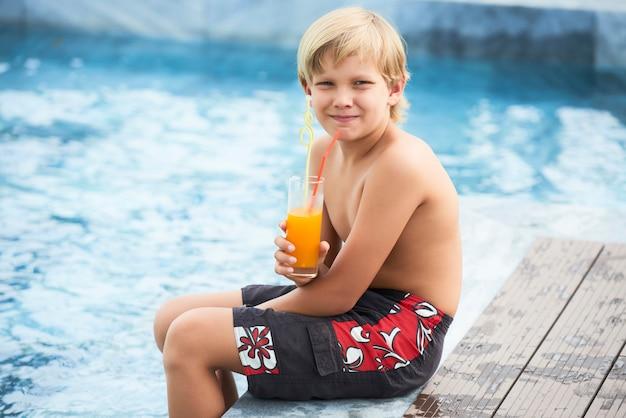 Мальчик пьет сок у бассейна