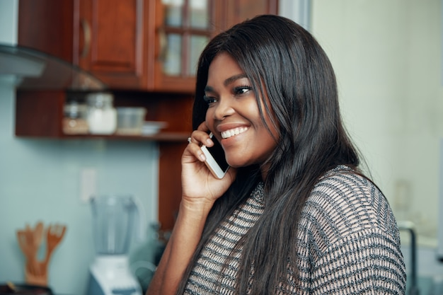 Счастливая чернокожая женщина имея телефонный звонок дома