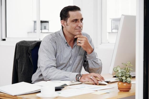 Человек с помощью компьютера в офисе