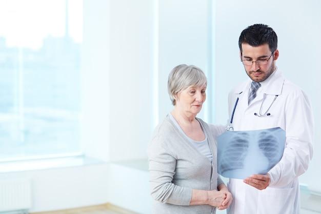 Врач показывает рентгеновский снимок для пожилых пациентов