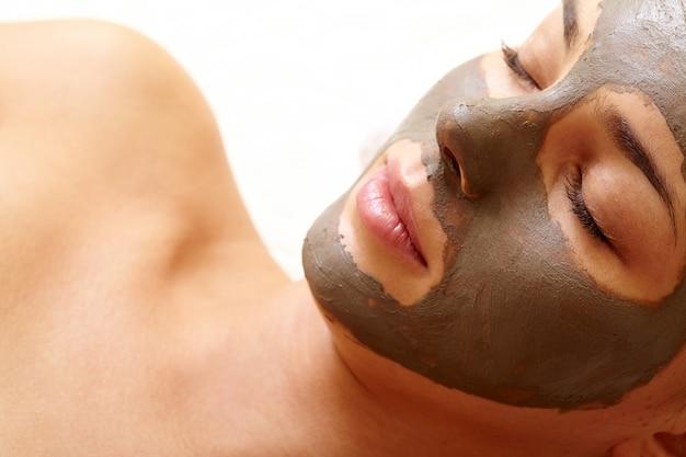 顔の皮膚を精製する若い女性のクローズアップ