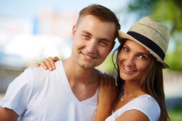 Улыбаясь пара идет по улице в летнее время