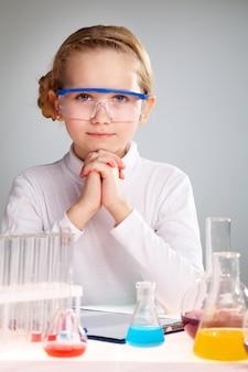 化学のためのフラスコに満足して少女