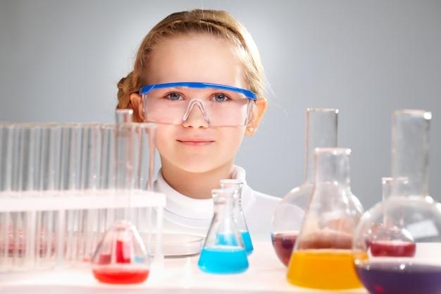化学のためのフラスコと笑顔少女