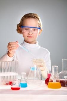 女の子は、青色の液体の入ったフラスコを保持します