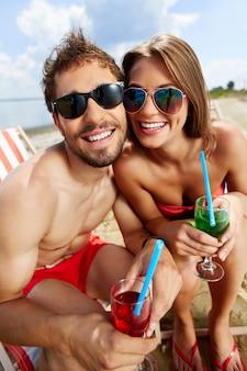 ビーチで幸せなカップル飲むカクテル