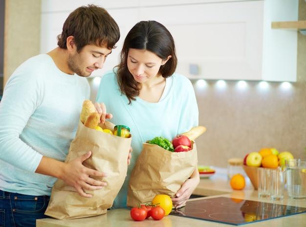 自宅で買い物袋を持つ若い夫婦