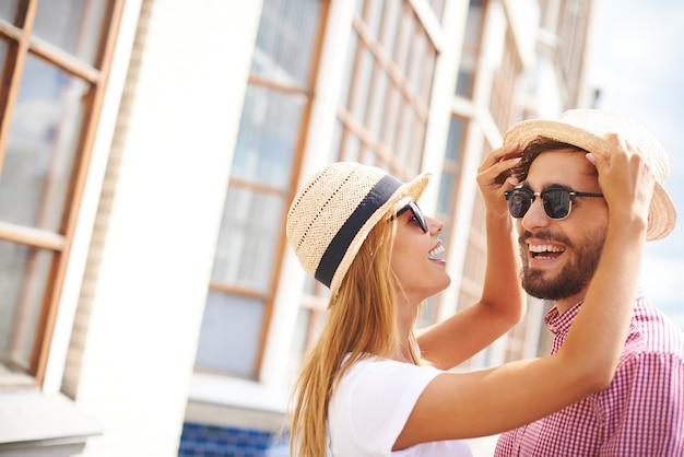 帽子と一緒に遊んで幸せなカップル