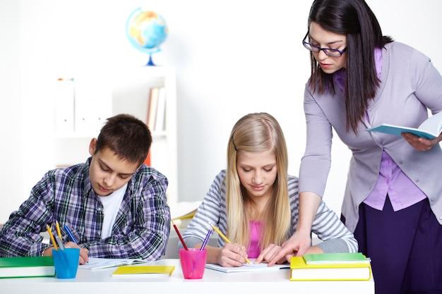生徒のノートブックの間違いを訂正する教師