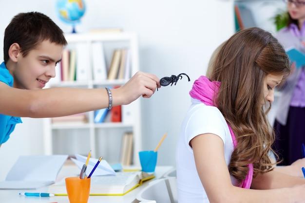 クラスメートの背後にあるクモと少年