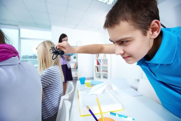 Парень держит паука в своем классе