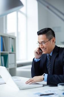 Бизнесмен говорить и печатать на ноутбуке