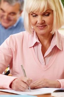 Пенсионеры женщина сосредоточена на ее эссе