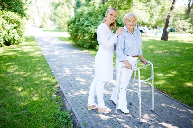 シニア女性が歩行フレームを使用するのを助けるナース