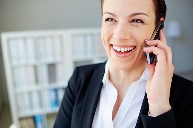 携帯電話と笑顔の女性のクローズアップ