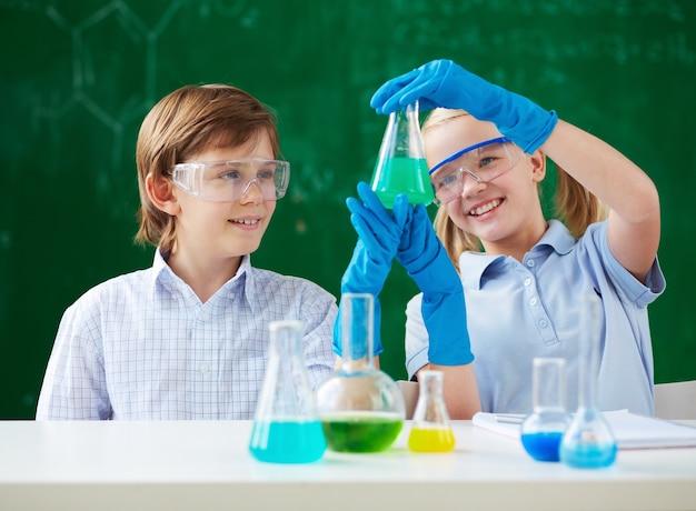 緑色の液体の入ったフラスコを保持している学生