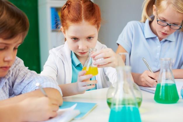 化学のクラスでフラスコを分析少女