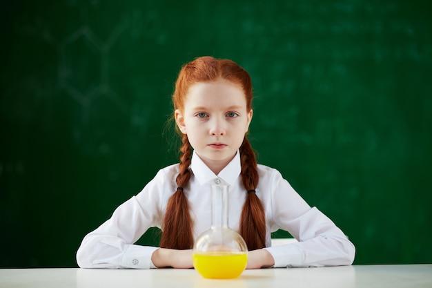 黒板の背景を持つ化学のクラスの学生