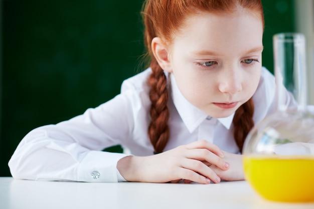 Крупным планом студента анализа колбу с оранжевой жидкости