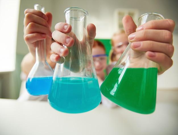 液体とフラスコを保持している学生のクローズアップ